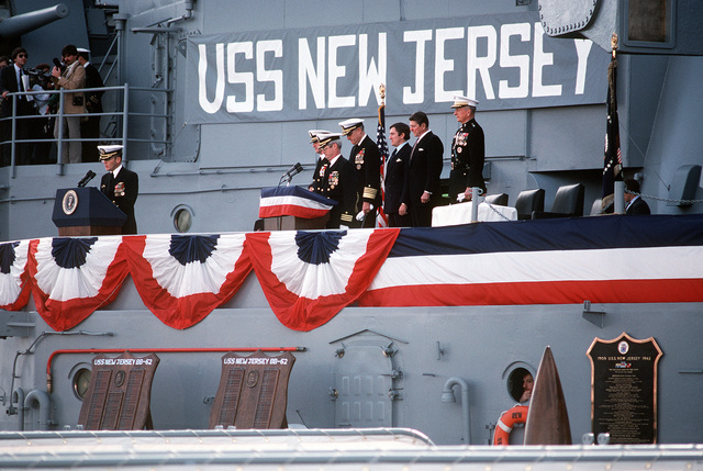 Chaplain (Cmdr.) Benny J. Hornsby gives the invocation at the recommissioning ceremony for the battleship USS NEW JERSEY (BB-62). Other guests are, from left to right: Capt. W. M. Fogarty, commanding officer; Cmdr. R. B. McKenna, executive officer; Chief of Naval Operations Adm. J.D. Watkins; Secretary of Navy John F. Lehman Jr. and President Ronald Reagan