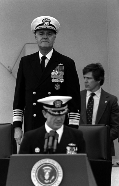 CHIEF of Naval Operations ADM James D. Watkins stands behind CAPT William M. Fogarty, commanding officer, during the recommissioning ceremony for the battleship USS NEW JERSEY (BB-62)