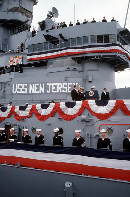 Right to left: President Ronald Reagan, CAPT William M. Fogarty, commanding officer; Chief of Naval Operations, ADM James D. Watkins and Secretary of the Navy John F. Lehman, Jr. stand on the speakers platform during the recommissioning ceremony for the battleship USS NEW JERSEY (BB-62). Crewmen line the rail the lower deck