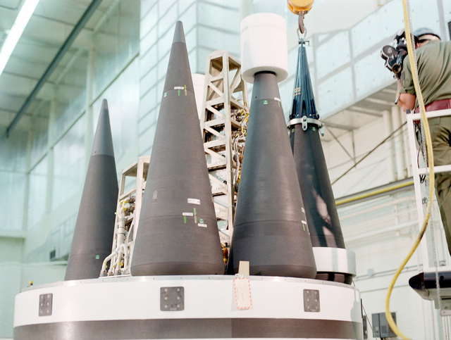 A close-up view of re-entry vehicles being positioned on the post-boost vehicle of an MX intercontinental ballistic missile in the preassembly building
