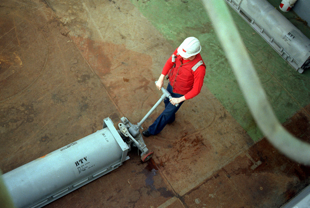A crewmember uses a dolly to move an RIM-7 Sea Sparrow missile into position for storage aboard the aircraft carrier USS KITTY HAWK (CV-63). The aircraft carrier is in Bremerton for a yard period