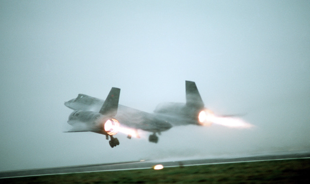 A ground-to-air left rear view of an SR-71 Blackbird aircraft taking off from a fog-shrouded runway. The SR-71 is flown by Det. 4, 9th Strategic Reconnaissance Wing, 3rd Air Force, RAF Mildenhall