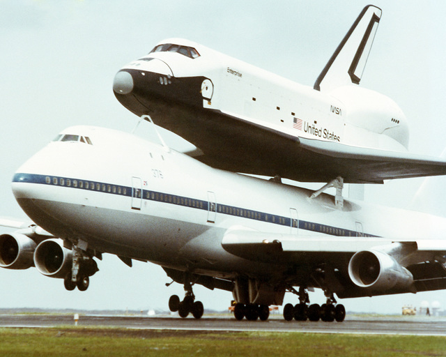 A left front view of a Boeing 747 aircraft landing to refuel while carrying the Space Shuttle Orbiter Enterprise (OV-101) on its back