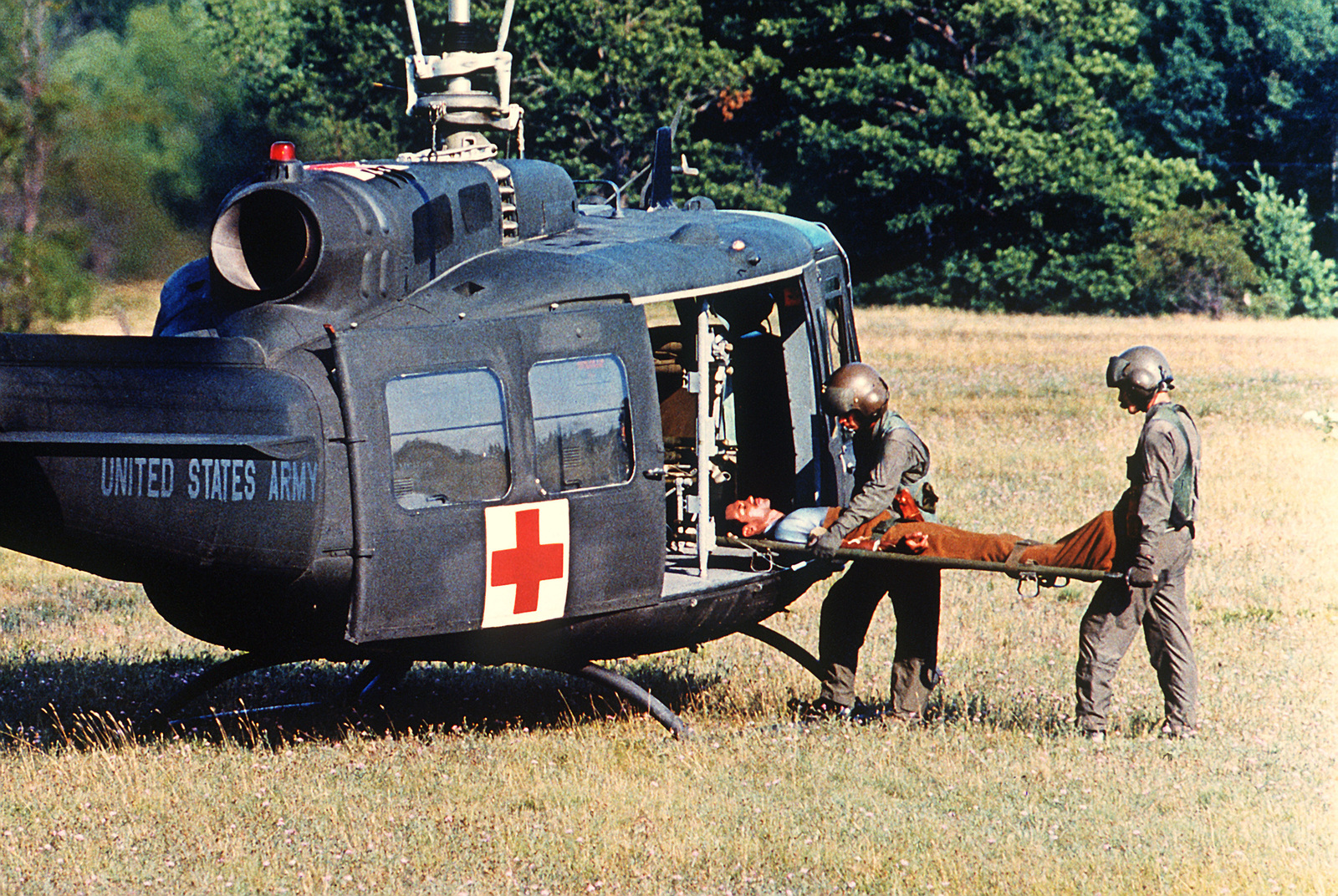 A medical evacuation (MEDEVAC) flight crew loads a patient on a stretcher aboard a UH-1 Iroquois helicopter for evacuation to a medical facility during a simulation exercise