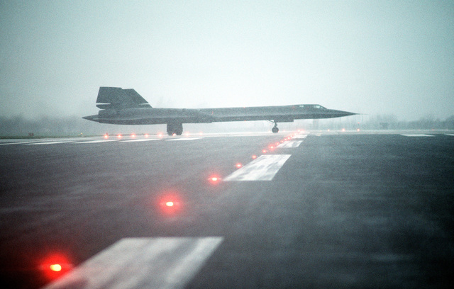 A right side view of an SR-71 Blackbird aircraft on a fog-shrouded runway. The SR-71 is flown by Det. 4, 9th Strategic Reconnaissance Wing, 3rd Air Force, RAF Mildenhall