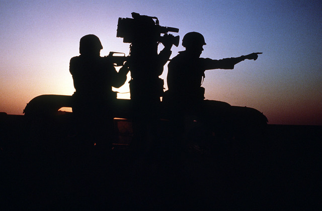 A silhouetted view of an Aerospace Audiovisual Service videographer, with video camera, a project officer and a rifleman during a location assignment. Exact Date Shot Unknown