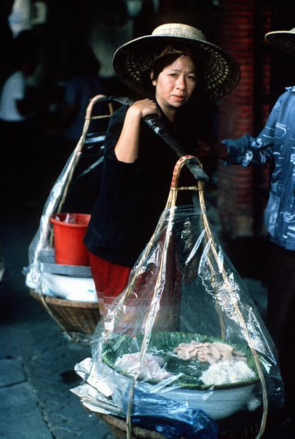 A view of a Thai woman as she shops at a sidewalk market