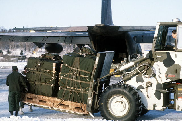 Air Force and Army personnel work together to load supplies aboard a C-130 Hercules aircraft. The supplies will be airlifted to troops in the field during exercise Brim Frost '83