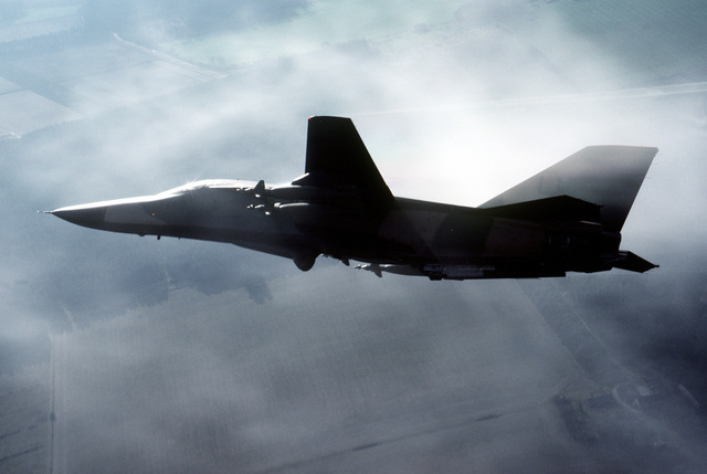 An air-to-air left side view of an F-111 aircraft flown by the 48th Tactical Fighter Wing, RAF Lakenheath