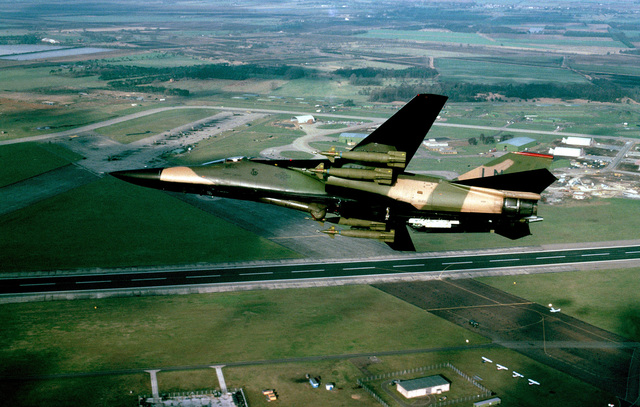 An air-to-air left underside view of an F-111 aircraft, armed with four bombs on its wing pylons. The aircraft is assigned to the 48th Tactical Fighter Wing, RAF Lakenheath