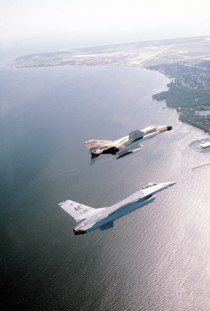 An air-to-air right side view of an F-4 Phantom II (background) and an F-16 fighter aircraft (foreground), over Tampa Bay