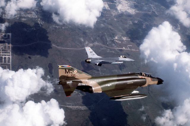 An air-to-air right side view of an F-4 Phantom II (foreground) and an F-16 fighter aircraft (background), over Tampa Bay