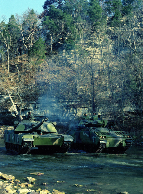 An M-1 Abrams main battle tank operated by the 1ST Plt., E Trp, 2nd Bn., 6th Cav., and an M-2 Bradley infantry fighting vehicle, operated by the 3rd Plt., E Trp., 2nd Bn., 6th Cav., are parked side by side at the U.S. Army Armor Center
