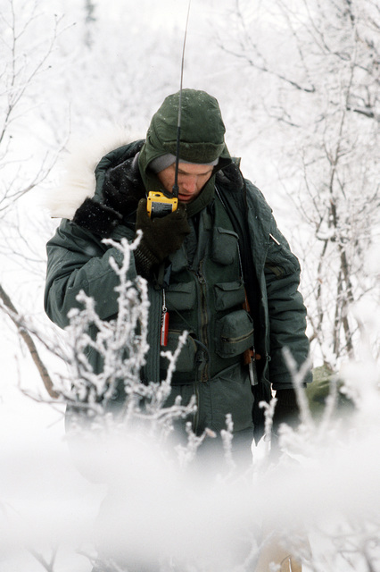 "MAJ. Brooke Myers attempts to establish radio contact with ""friendly forces"" after he was dropped off in the woods during a search and rescue exercise conducted as part of exercise Brim Frost '83"