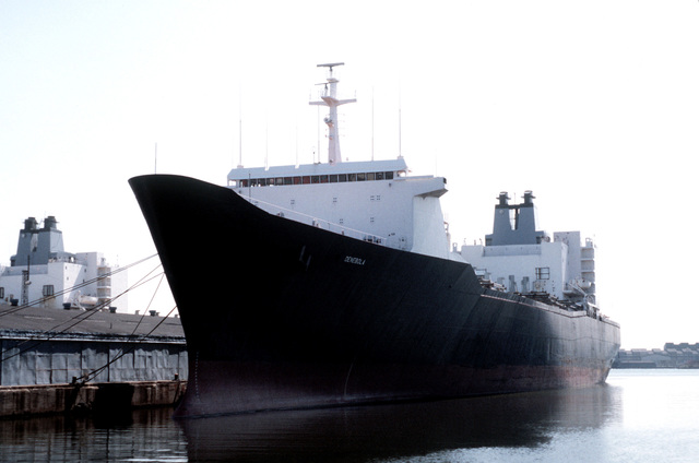 Port bow view of the Military Sealift Command cargo ship DENEBOLA (T-AK-289), tied to the pier
