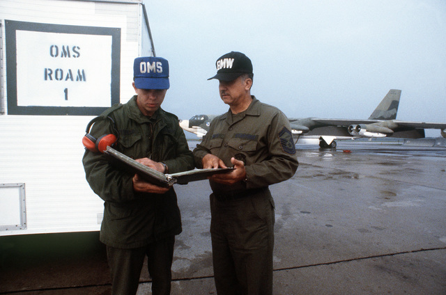 SGT Karl Dittfield, left, a B-52 Stratofortress aircraft crew chief, and CSM Henry T. Coste Jr., Recovery Oriented Aircraft Maintenance (ROAM) chief, discuss aircraft maintenance next to a flight line trailer. The ROAM system is designed to ensure that aircraft receive vital service immediately after completing a mission