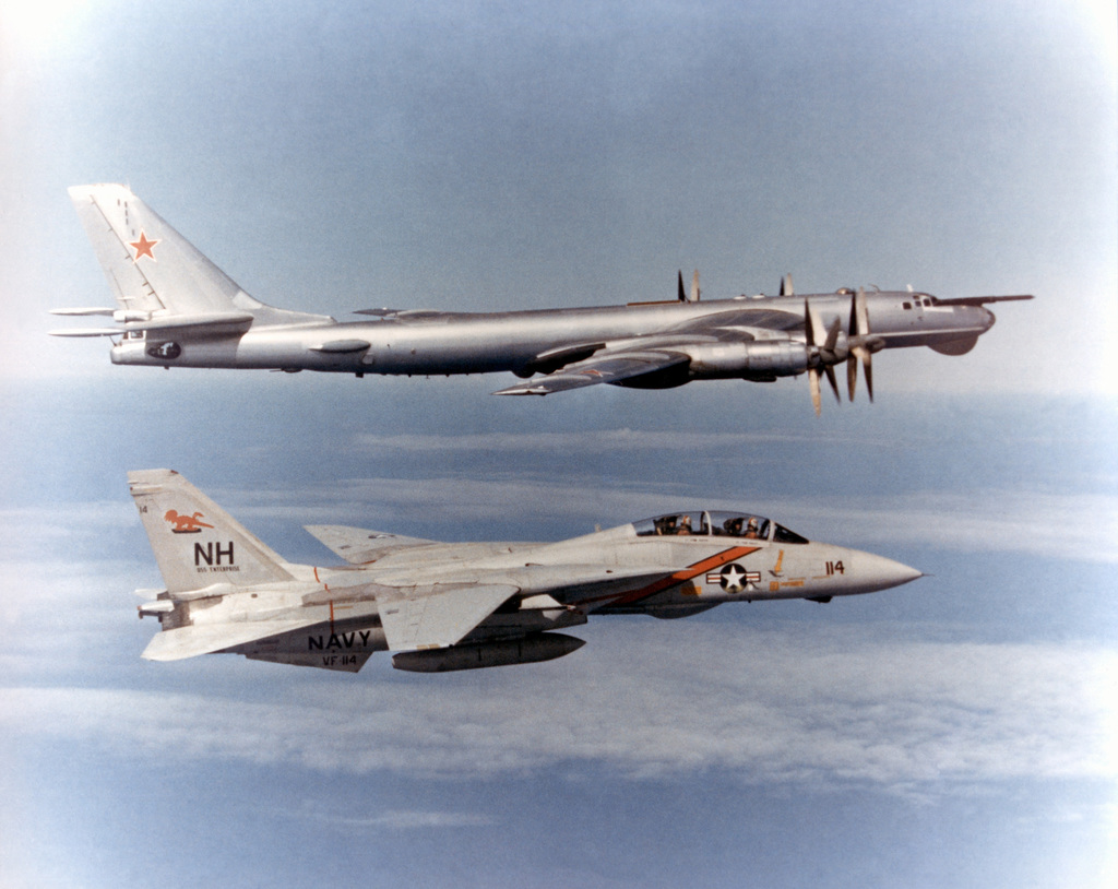Starboard view of an F-14A Tomcat, Fighter Squadron (VF)-114, Aardvarks, Naval Air Station (NAS) Miramar, California, alongside a Soviet TU-95RT Bear D (Tupolev) maritime patrol aircraft. Exact date photo taken not known