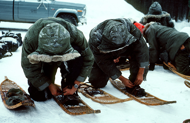 Students of the Navy's Cold Weather Environmental Survival Training fasten snow shoes onto their boots during a survival course being taught to them by instructors from the Fleet Aviation Specialized Operational Training Group Atlantic (FASO)