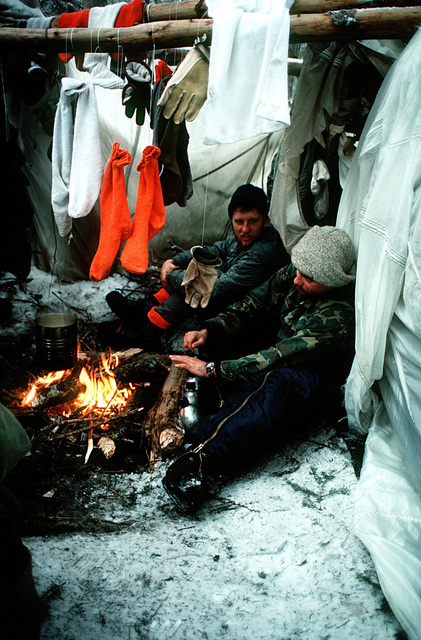 Students of the Navy's Cold Weather Environmental Survival Training warm themselves by a fire inside their cold weather shelter. The students are being taught survival techniques by instructors from the Fleet Aviation Specialized Operational Training Group Atlantic (FASO)