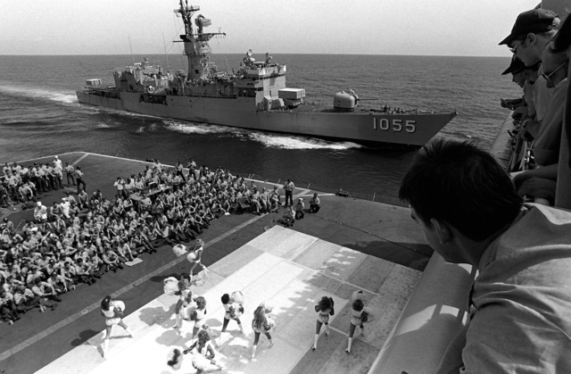 "The Dallas Cowboy Cheerleaders perform their USO show ""America and Her Music"" on the deck of the fast combat support ship USS SACRAMENTO (AOE-1). The frigate USS HEPBURN (FF-1055) maneuvers off the port side of the SACRAMENTO"
