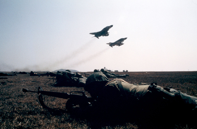 Two F-4 Phantom II aircraft take off simultaneously during exercise TEAM SPIRIT '82. Members of the 3380th Security Police Squadron (foreground) defend the air field from the aggressor force