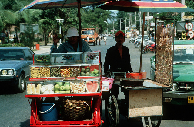 Vendors sell fruit and Thai food from their carts on a busy street