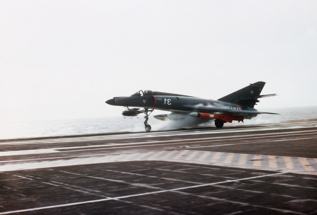 A right front view of a Super Entendard aircraft being launched from the flight deck of the French aircraft carrier FOCH (R-99). Mounted on the aircraft's right wing pylon is an AM-39 Exocet air-to-surface missile. The FOCH is deployed off the coast of Lebanon