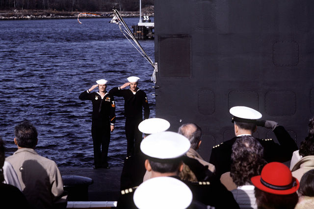Two crewmen salute the colors aboard the nuclear-powered attack submarine USS CITY OF CORPUS CHRISTI (SSN-705) during commissioning ceremonies. The ship was built by the Electric Boat Division, General Dynamics Corporation
