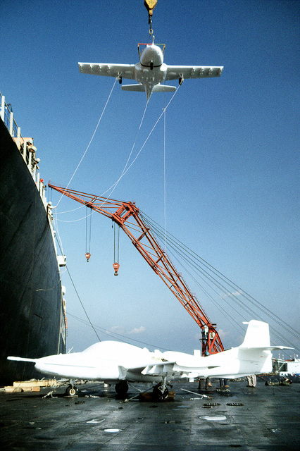 A floating crane lowers the second A-37 Dragonfly aircraft from the container ship Tyson Lykes to a Navy barge. The aircraft will have their protective covers removed and will be reassembled at the U.S. Naval Auxiliary Landing Field, Kisarazu, Japan, prior to being flown to Osan Air Base, South Korea. They will be used as maintenance trainers