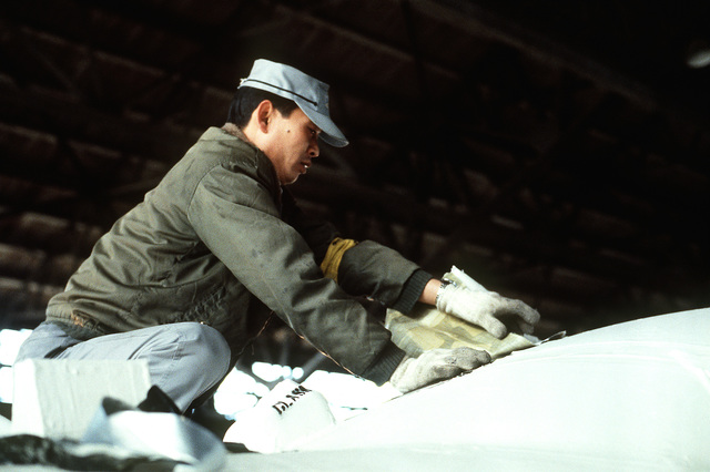 A workman from the Japan Aircraft Company removes the protective cover from an A-37 Dragonfly aircraft. After being reassembled, the aircraft will be flown to Osan Air Base, South Korea, to be used as a maintenance trainers