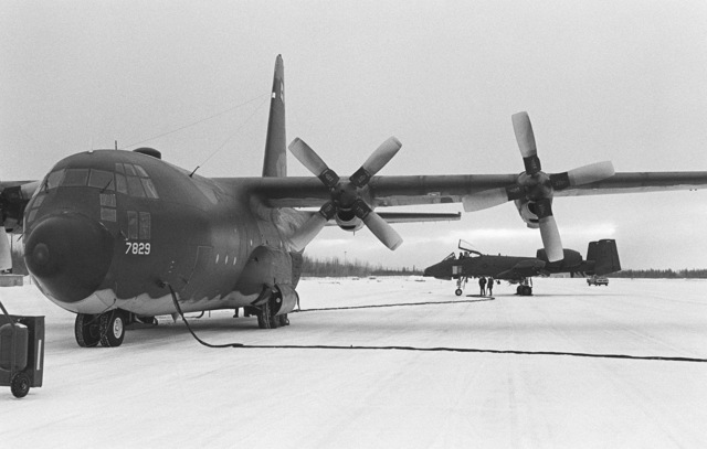 A C-130 Hercules aircraft from Elmendorf Air Force Base, Alaska, refuels an A-10 Thunderbolt II aircraft while on the runway. The C-130 carries two fuel bladders in its cargo area