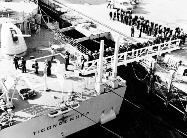 Crewmen file aboard the aft gangplank on the guided missile cruiser USS TICONDEROGA (CG-47)