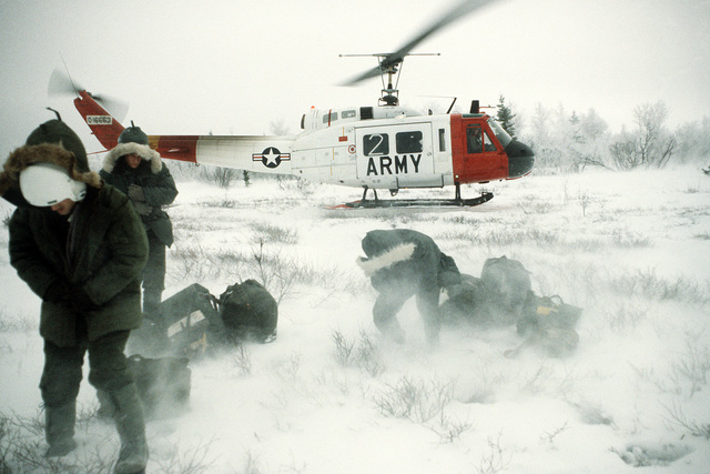 Air Force personnel begin a search and rescue exercise after arriving in a wilderness area via an Army UH-1 Iroquois helicopter during exercise Brim Frost '83