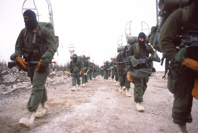 Infantrymen equipped with arctic field gear march down a road during Exercise Brim Frost '83