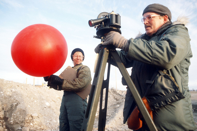 STAFF Sergeant John T. Ferguson and SENIOR Airmen Jo Anne Dahlen of the 208th Weather Flight, Minnesota Air National Guard, prepare to launch and track a weather balloon during Exercise Brim Frost '83