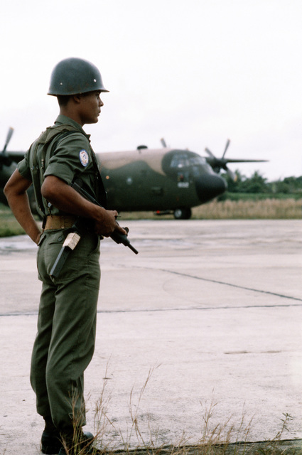 """A Honduran Air Force security guard stands sentry duty near a C-130 Hercules aircraft of the 773rd Tactical Airlift Squadron during the combined United States/Honduran training operation """"AHUAS TARA"""" (BIG PINE)"""