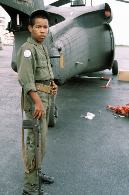 """A Honduran Air Force security guard stands sentry duty next to a partially assembled United States Army UH-60 Blackhawk helicopter during the combined United States/Honduran training operation """"AHUAS TARA"""" (BIG PINE)"""