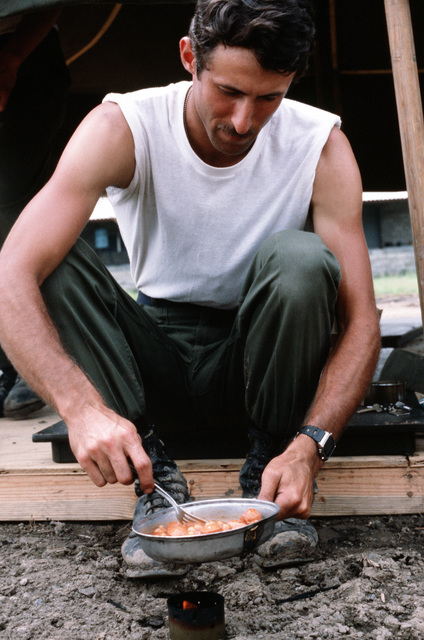 "AIRMAN 1ST Class Dan Avara heats his dinner over a homemade stove during the combined United States/Honduran training operation ""AHUAS TARA"" (BIG PINE)"