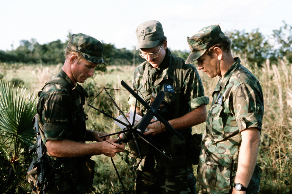 """Members of the combat control team (CCT) set up a satellite communications antenna near a drop zone during the combined United States/Honduran training operation """"AHUAS TARA"""" (BIG PINE). From left to right, they are: SENIOR AIRMAN Libby, 1ST Lieutenant Robert Stephan and Master Sergeant Dalton"""