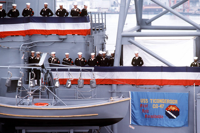 Crew members man the rail aboard the first Aegis guided missile cruiser USS TICONDEROGA (CG-47) during commissioning ceremonies at Ingalls Shipbuilding
