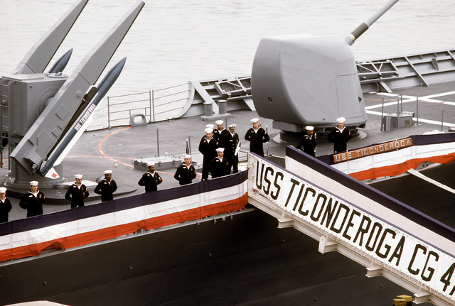 Crew members man the rail aboard the first Aegis guided missile cruiser USS TICONDEROGA (CG-47) during commissioning ceremonies at Ingalls Shipbuilding. The twin Mark 26 Mod One missile launcher with Standard medium range surface-to-air missiles (left), and a five-inch DP Mark 45 gun are visible behind them