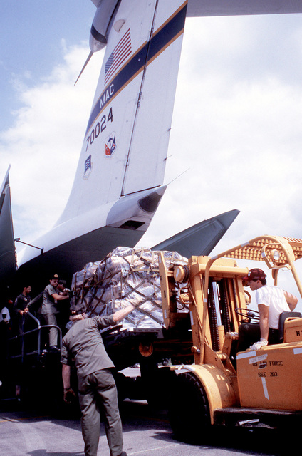 A forklift is used to load a pallet of supplies into the rear cargo bay of a Military Airlift Command C-141B Starlifter aircraft. The C-141B is being prepared for a flight to Honduras in support of the joint United States/Honduran exercise AHUAS TARA (BIG PINE)