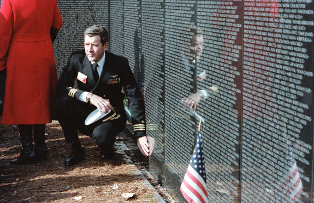 A Navy commander reviews the names of US service casualties inscribed on the Vietnam Veterans Memorial. The commander is visiting the memorial of the National League of Families of American Prisoners and Missing in Southeast Asia