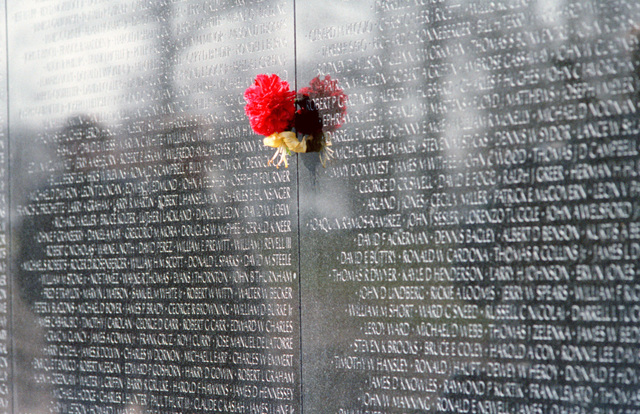 Inscriptions on the Vietnam Veterans Memorial honor the members of the US Armed Forces recognized as casualties of the Vietnam War. A flower is placed on the wall alongside the name of a deceased friend or relative by a member of the National League of Families of American Prisoners and Missing in Southeast Asia