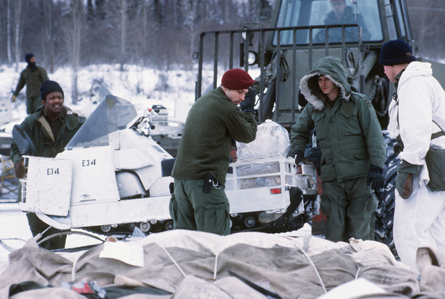 Members of Company C, 4th Battalion, 327th Infantry, from Richardson, off-load a snowmobile from a forklift during Exercise Brim Frost '83