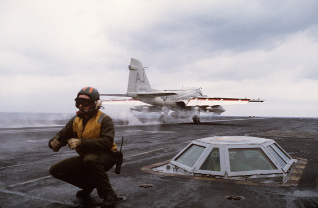A flight deck crewman positions himself against the blast from an A-6 Intruder as the aircraft is catapulted from the nuclear-powered aircraft carrier USS NIMITZ (CVN 68). The glass enclosure is the catapult launch station