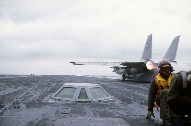 A flight deck crewman positions himself against the blast from an F-14 Tomcat as the aircraft is catapulted from the nuclear-powered aircraft carrier USS NIMITZ (CVN-68). The glass enclosure is the catapult launch station