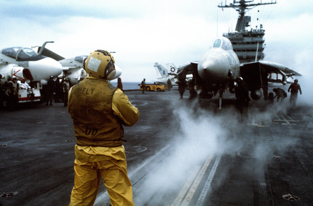 A plane director signals to the pilot of an F-14 Tomcat as other flight deck crewmen prepare the aircraft for catapulting from the nuclear-powered aircraft carrier USS NIMITZ (CVN 68)