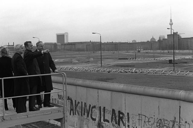 Vice President George Bush looks over the Berlin Wall into East Berlin during his tour through the city. He is escorted by Governing Mayor Von Weizacker and Chancellor Kohl