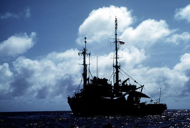 A port quarter view of the salvage ship USS BOLSTER (ARS 38), preparing to get underway off the coast of the island